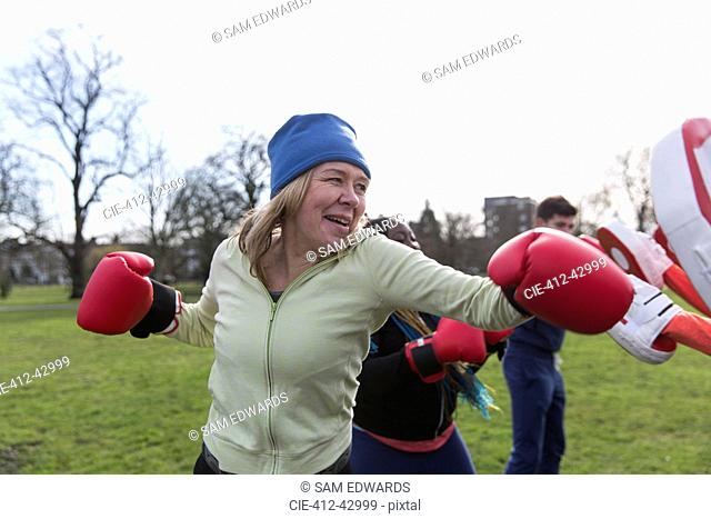 Determined senior woman boxing in park