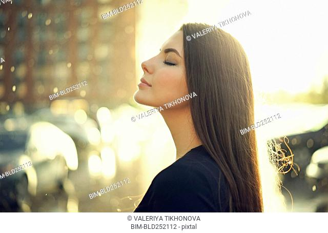 Profile of Caucasian woman outdoors with eyes closed