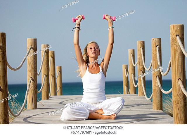 Healthy young woman exercising on a boardwalk