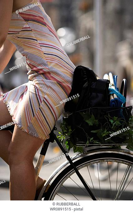 Mid section view of a woman riding a bicycle