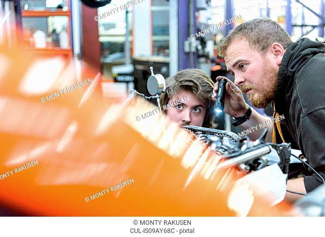 Engineer and apprentice adjusting engine in racing car factory