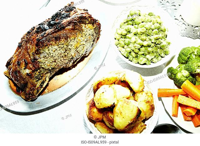 Dinner meal of roast meat with potatoes, carrots, broccoli and broad beans on table