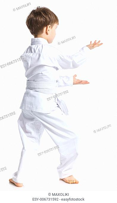 Aikido boy fighting position in white kimono isolated on white
