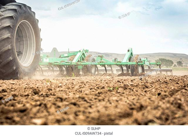 Surface level view of tractor and ploughing field