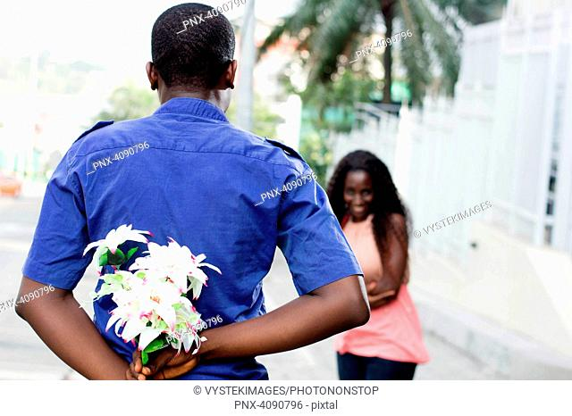 young man hides a flower in his back and give it to the young woman in surprise