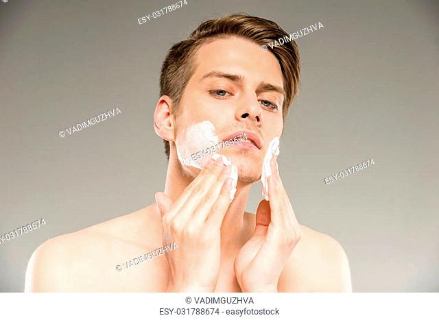 Portrait of a handsome young man is applying shaving cream to his face
