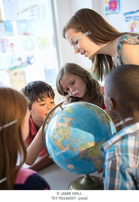 Children 8-9 with female teacher learning in classroom