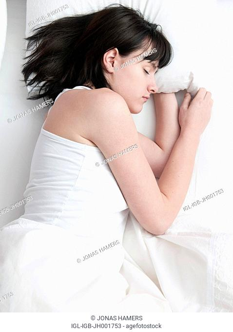 This picture shows a young caucasian woman with brown hair as she lies and sleeps in her bed
