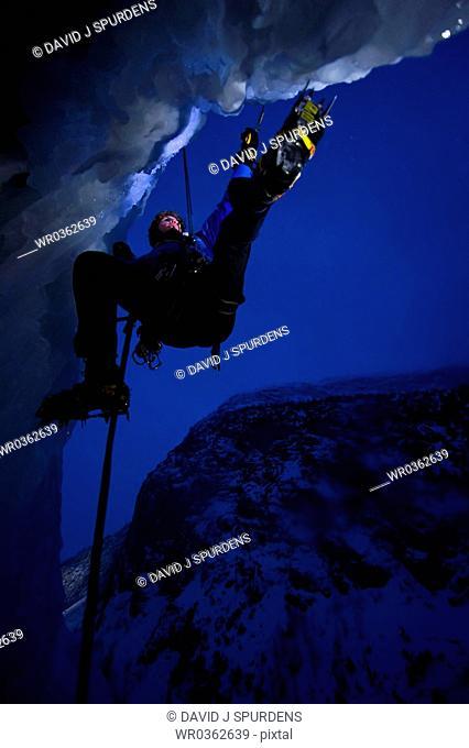 Ice climber climbing frozen waterfall at night