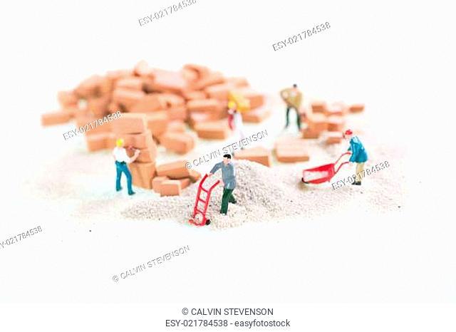 Miniature workmen doing construction brickwork top view close up