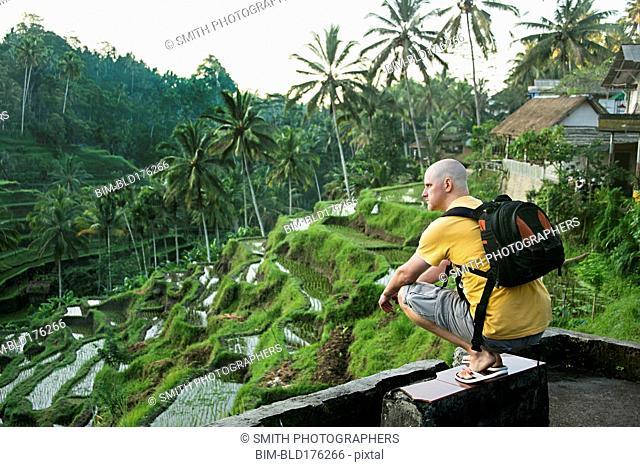 Caucasian tourist admiring rural rice terrace, Ubud, Bali, Indonesia