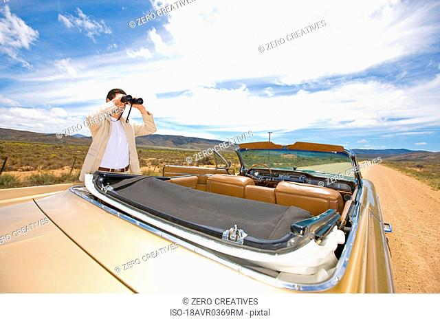 Lonely traveler using binoculars