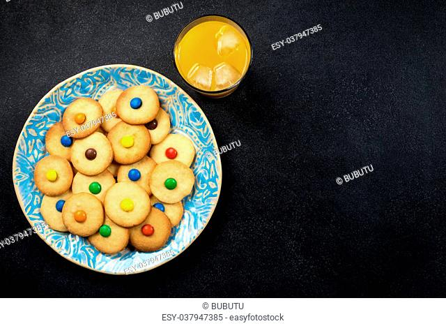 Homemade cookies on a plate, orange juice - on black background - copy space