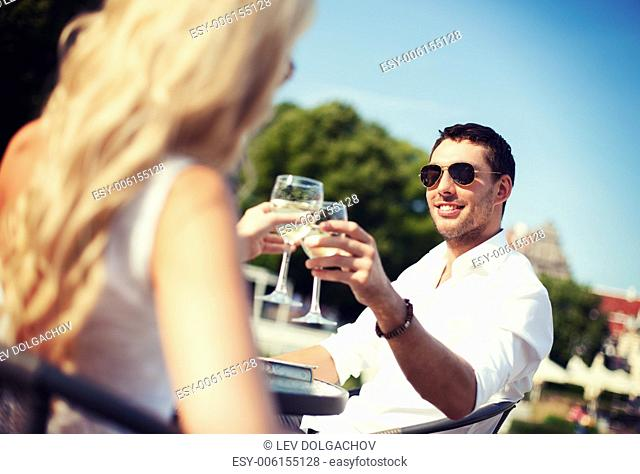 summer holidays and dating concept - man drinking wine with woman in cafe in the city