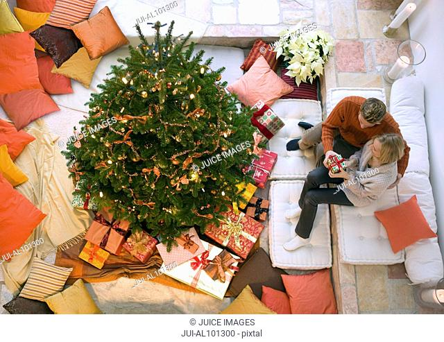 Overhead view of couple opening gifts near Christmas tree