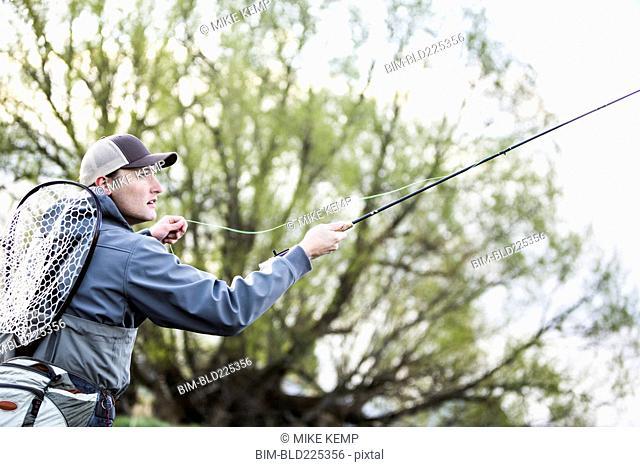 Caucasian man fly fishing