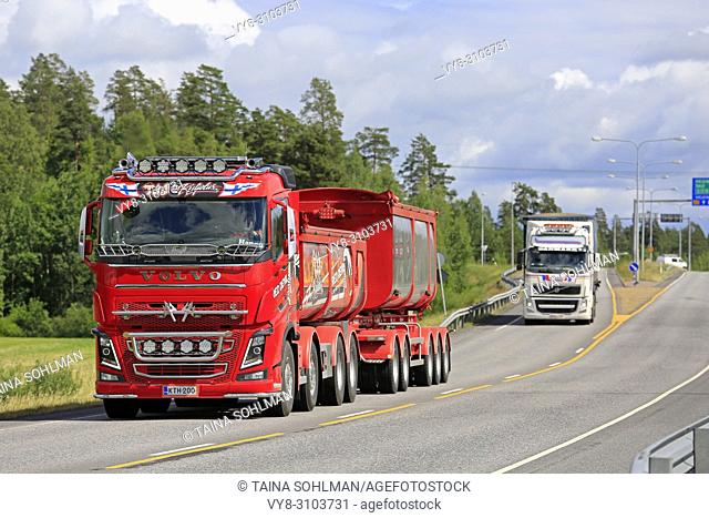 Volvo FH truck Red Devil of TJJ Kuljetus Oy for gravel haul on the road in summer with another Volvo transporter. Kaarina, Finland - June 29, 2018
