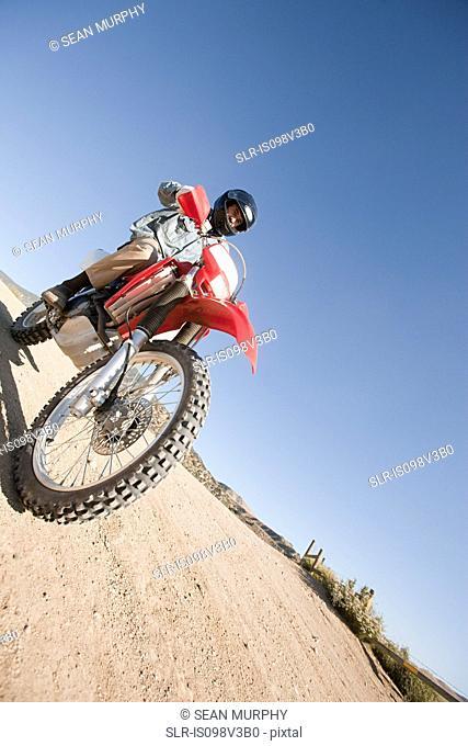 Man riding dirt bike on dirt track