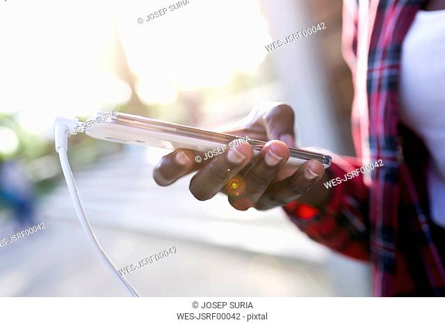 Woman's hand holding smartphone, close-up