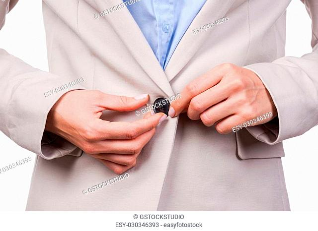Making business look great. Close-up of young businesswoman buttoning her jacket while standing against white background