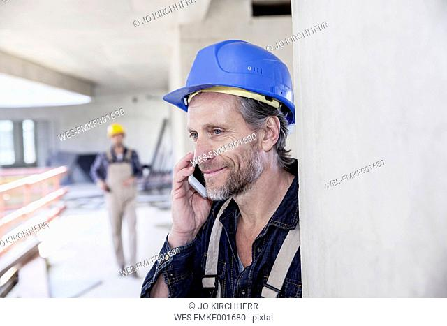 Smiling worker on construction site on cell phone