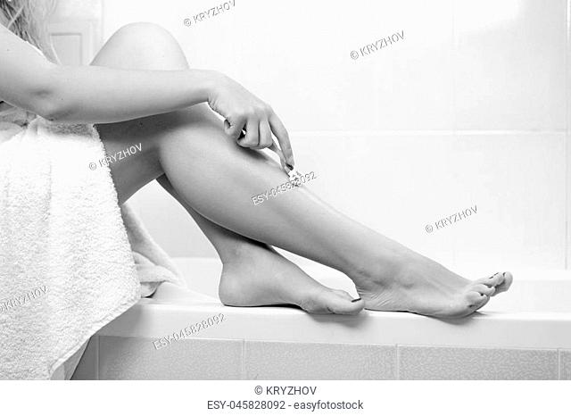Black and white image of young woman covered in bath towel shaving legs with razor