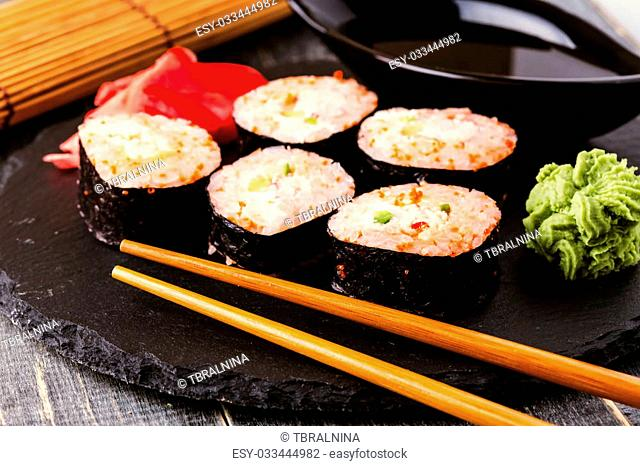 Sushi roll with crab, spicy sauce, cucumber and tobiko caviar, selective focus
