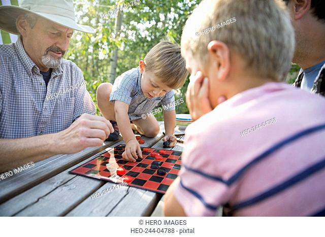 Multi-generation men playing checkers campsite picnic table