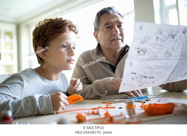 Grandfather and grandson viewing directions for model cars