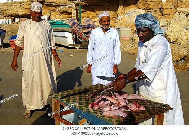 Fishmonger cutting fish for two Arab clients at an open-air market stall, Sur, Sultanate of Oman