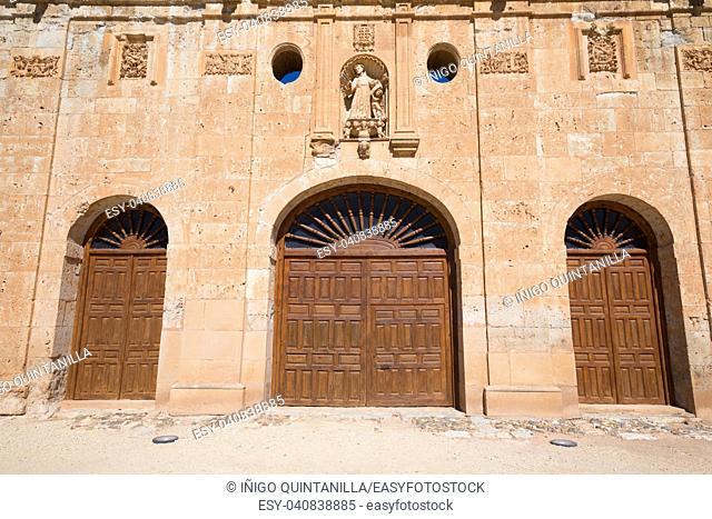 Landmark of facade, three old wooden doors and sculpture of San Francisco de Asis, in ancient convent, from thirteenth century, in Ayllon village, in Segovia