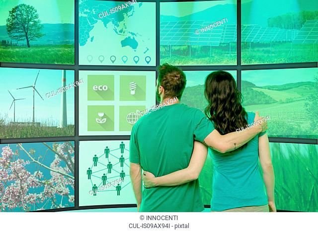 Young couple arms around each other, standing in front of graphical screens, displaying environmental images
