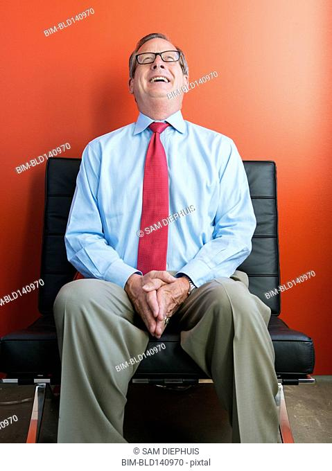 Caucasian businessman laughing in chair