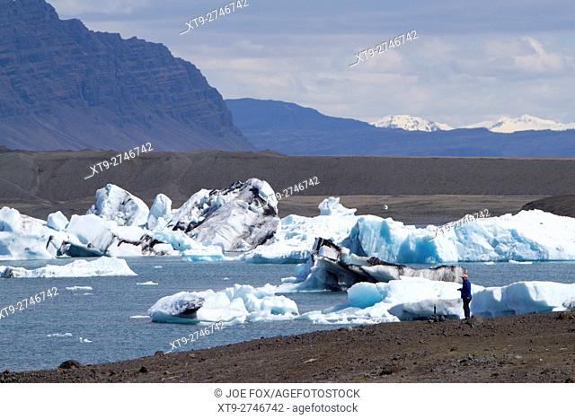 tourist with camera on glacial moraine jokulsarlon glacial lagoon with icebergs southern iceland