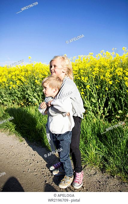 Full length of smiling girl embracing brother at rapeseed field