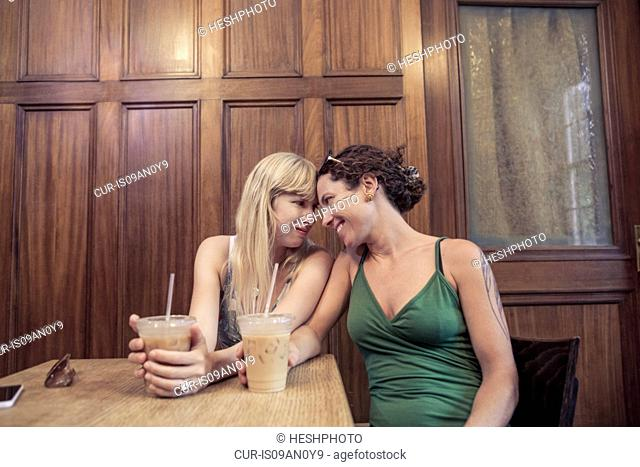Two women face to face sharing intimacy in cafe