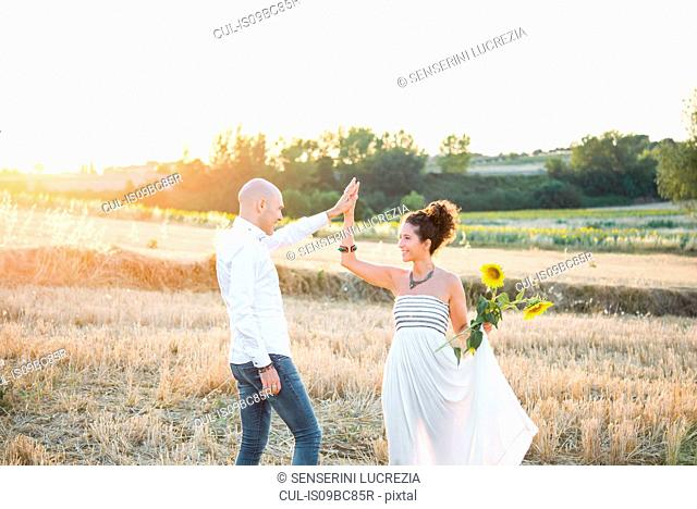 Heterosexual couple dancing in fields, woman holding sunflowers in hand