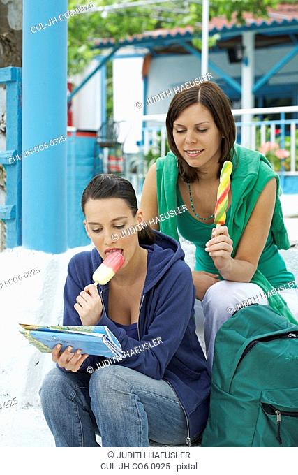 Two smiling women sitting on steps while looking at map and eating Popsicles