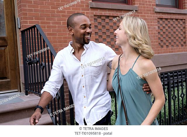 Smiling couple walking in residential district