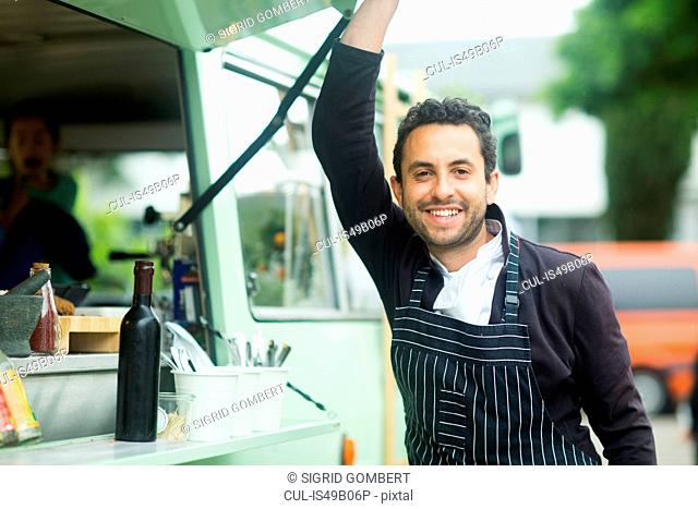 Portrait of small business owner opening van food stall hatch