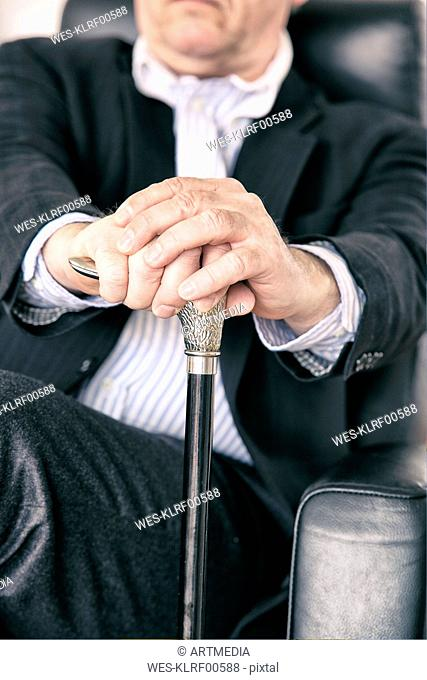 Hands of senior sitting on black leather chair holding silver handle of walking stick, close-up