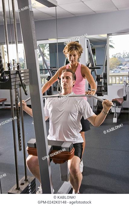 Mature couple in workout clothes using weight machine at gym