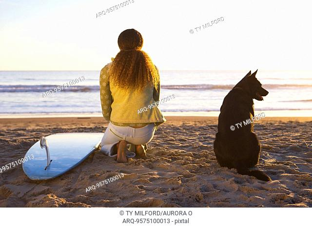 Surfer woman and dog on beach