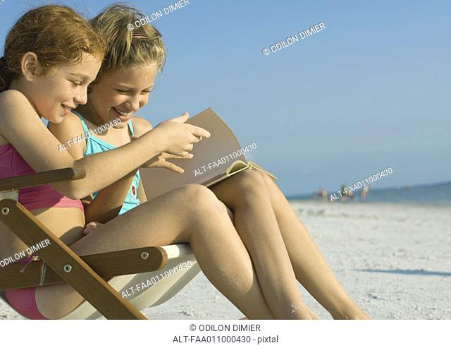 Girls reading book together on beach