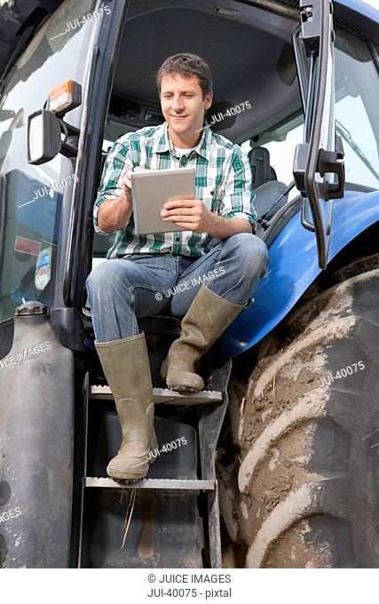 Farmer Sitting In Cab Of Tractor Using Digital Tablet