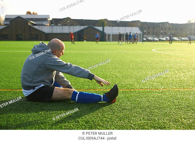 Football player stretching before game