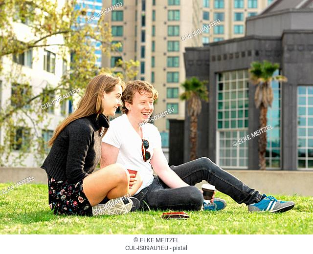 Young couple having coffee break on grass, Melbourne, Victoria, Australia