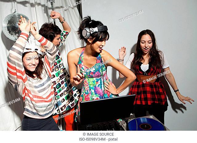 Disc jockey wearing headphones at party