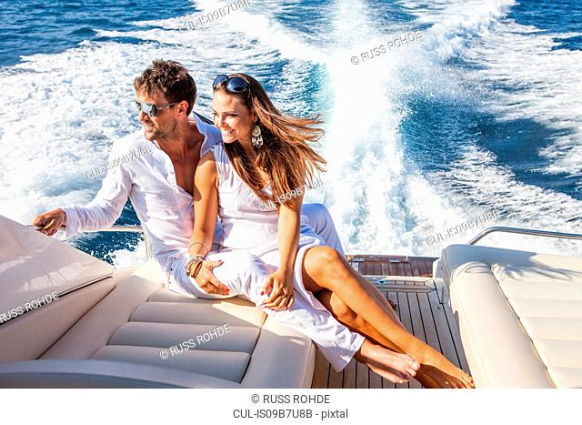 Couple relaxing on yacht, on water, looking at view
