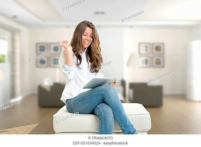 Young woman sitting at home using a digital tablet
